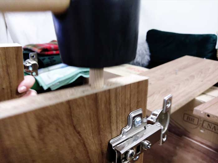 木ダボを木製ハンマーで叩いて入れる